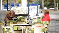 People sitting on the terrace of a bar on a promenade one sunny morning Stock Footage