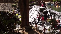 People bathe in clear rocky spring river water Stock Footage