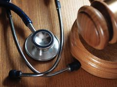 Judge gavel and stetaskop on wooden background Stock Photos