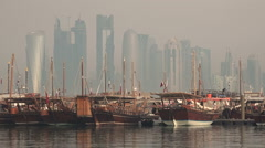 Qatar, Doha city skyline behind classic dhow vessels Stock Footage