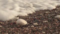 Pebble beach with sea foam Stock Footage