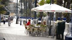 People sitting on the terrace of a bar on a walk one sunny morning. Stock Footage