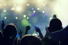 Cheering crowd in front of stage lights - retro photo - stock photo