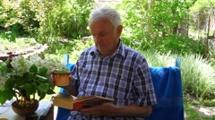 An elderly man sitting and reading a book and drinking juice in outdoor garden Stock Footage