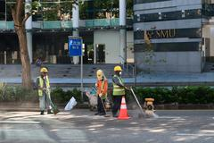Construction workers repair pavement on a downtown street. Stock Photos
