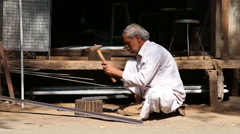 Indian man shaping rod at the street while vehicles and people pass. Stock Footage
