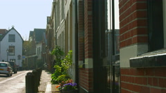 Old man passing by with its bicycle on Nieuwe Raamstraat Haarlem Netherlands Stock Footage