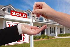 Stock Photo of Handing Over the House Keys in Front of Sold New Home Against a Blue Sky