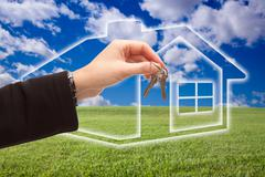 Female Handing Over Keys on Ghosted Home Icon, Grass Field, Clouds and Sky. - stock photo