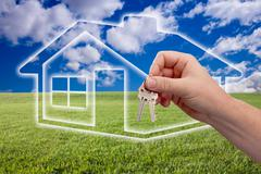 Male Handing Over Keys on Ghosted Home Icon, Grass Field, Clouds and Sky. - stock photo