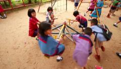Kindergarten students in regional costume playing carousel in the playground. NA Stock Footage