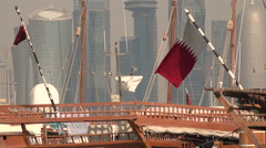 Qatar flags wave on dhow vessels, before the Doha city skyline Stock Footage