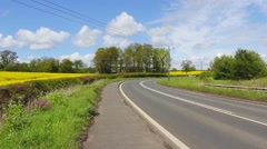 Busy road in Scotland with rapeseed fields on the sides Stock Footage