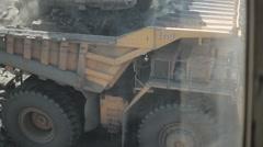 Unload rocks from excavator bucket to big dump truck Stock Footage
