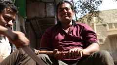 Portrait of Indian man with mallet in hands, with friends sitting aside. Stock Footage