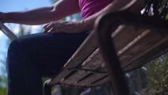 Man sitting on a bench with his laptop 2 video in 1 Stock Footage