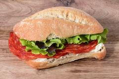 sandwich salami, gorgonzola and salad on wooden table - stock photo