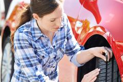 Woman Checking Tread On Car Tyre With Gauge Stock Photos