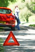 Female Driver Broken Down On Country Road With Warning Sign In F - stock photo