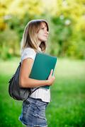 Young female student with workbook standing on green blurred grass background - stock photo