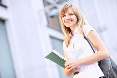 Young student, beautiful caucasian woman standing on blurred university build Stock Photos
