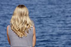 Stock Photo of Young woman in sailor's shirt standing on pier and looking away