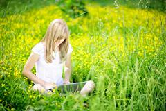 Young Caucasian woman using Laptop (Netbook) on nature, sitting in the grass  Stock Photos