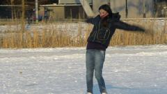 Girl on ice skates runs and falls Stock Footage