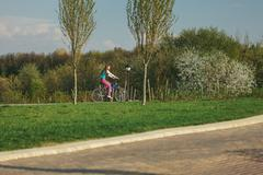 Young woman riding on bicycle in park Kuvituskuvat