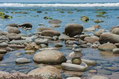 Stack of rocks delicately balanced at low tide - stock photo