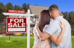 Military Couple in Front of House and Foreclosure For Sale Real Estate Sign. Stock Photos