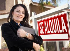 Female Hispanic Real Estate Agent, Se Alquila Sign and House Stock Photos