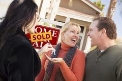 Hispanic Female Real Estate Agent Handing Keys to Excited Couple - stock photo
