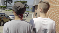 Gay Couple Walk Down Sidewalk Toward Waterfront Park Stock Footage