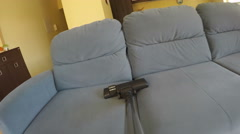 Dust hoovering from leather sofa with vacuum cleaner. 4K Stock Footage