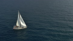 High angle - 2 sail and 1 motorboat passing in deep blue water. Stock Footage