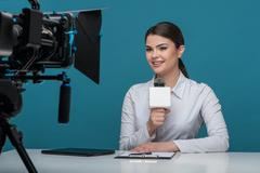 Beautiful girl tv newscaster with pretty smile reports - stock photo