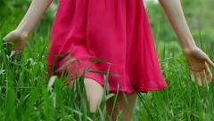 Beautiful, attractive red-haired girl runs across the grass Stock Footage