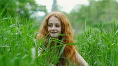 Beautiful, attractive girl with curly hair walks in the woods and enjoy nature - stock footage