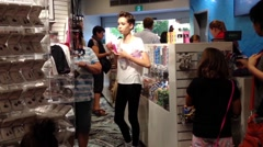 People buying gift accessory inside Vancouver aquarium gift shop. - stock footage