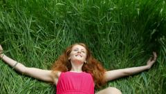 Beautiful, attractive young girl falls into the grass - stock footage