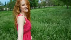 Attractive girl running on the grass in the forest, holding his friend's hand Stock Footage