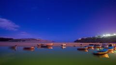 Lagoon stars starlapse night sky astronomy boats coast ocean moulay bousselham Stock Footage