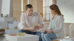 Lucky young man earned lots of money, happy wife hugging husband Stock Footage