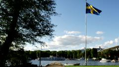 Boat passing behind Swedish flag Årsta 1030 Stock Footage
