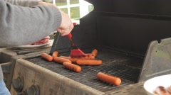 A man cooking hamburgers and hotdogs on barbecue Stock Footage
