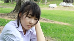 Sad Unhappy thai student teen Sitting On Park Stock Footage