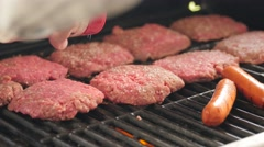 A man seasoning hamburgers and hot dogs on grill Stock Footage