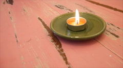 Flaming candle on red wooden table Stock Footage