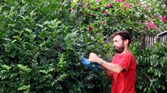 Hairy Australian male cutting a hedge with an electric trimmer Stock Footage